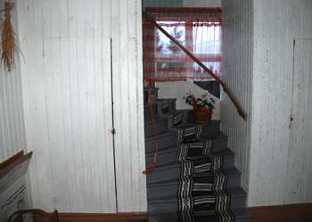 En ganska smal och brant trappa leder från hallen upp till ovanvåningen